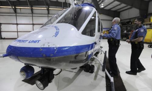 Colorado Springs Police Dept. helicopter pilots Barry Worstell and Jacob Reutner (left to right) look over one of the two helicopters of the CSPD. The helicopters are being sold and the program is being shut down. Tuesday, December 22, 2009.  (The Gazette/Jerilee Bennett)  - for winnipeg free press
