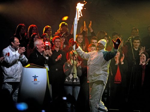 Brandon Sun Community torch bearer Bernie Chrisp carried the Olympic torch on stage to light the community cauldron during Friday night's celebration in the Manitoba Room. (Bruce Bumstead/Brandon Sun)