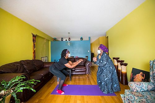 MIKAELA MACKENZIE / WINNIPEG FREE PRESS  Mwaka Kaonga and her mom, Phillis Nachilongo, demonstrate the workout that Phillis has been doing since last year at the start of the lockdown at their home in Winnipeg on Wednesday, Feb. 24, 2021. For Sabrina Carnevale story.  Winnipeg Free Press 2021
