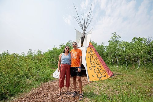 MIKE SUDOMA / Winnipeg Free Press Artist Jordan Stranger and his partner, Janelle Wride, stand with a tipi Stranger created that dipicts the seven sacred teachings at Fort Whyte Friday afternoon.  July 30, 2021