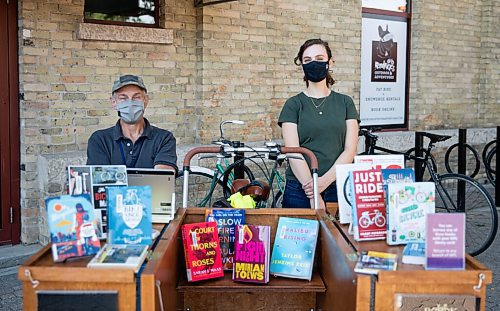 JESSICA LEE/WINNIPEG FREE PRESS  Workers for Winnipeg Library Hugh O'Donnell (left) and Toby Cygman (right), pose for a photo on September 13, 2021, at The Forks.  Winnipeg Bike Week kicks off at The Forks on September 13, 2021. Winnipeg Bike Week usually takes place in June, but due to COVID this year, organizers moved it to September.