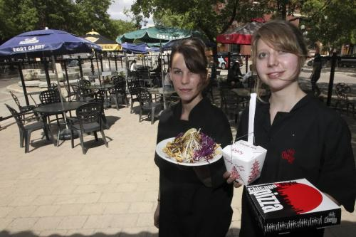 MIKE.DEAL@FREEPRESS.MB.CA 100707 - Wednesday, July 07, 2010 -  Restaurant review The Line-up restaurant in the Exchange. (l-r) Servers Samantha Mauws, with salad and Ava Glendinning, with take-out noodles and pizza, on the patio of the Line-Up where you can see the new Exchange stage. MIKE DEAL / WINNIPEG FREE PRESS