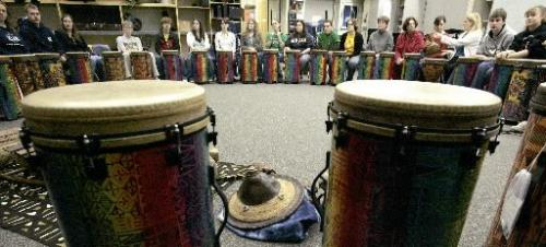 """Grade 10 students share African artifacts during an African drumming lesson at College Jeanne Sauve on Sunday afternoon. Berthelette, who is with the """"Tassu Percussion"""" group, was instructing the students - who are part of Students Without Borders Afrique 2007 - part of the African culture. For story by Lindor Reynolds. Photo by Marianne Helm/Winnipeg Free Press"""
